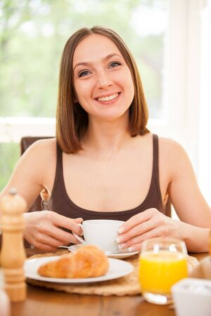 breakfast cup: Young woman is drinking a hot cup of coffee while having a breakfast at home Stock Photo