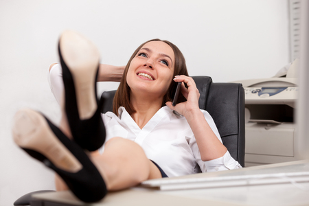Photo of smiling brunette businesswoman with legs on the desk phoning in office