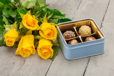 pralines: Photo of chocolate pralines with yellow roses over wooden table Stock Photo
