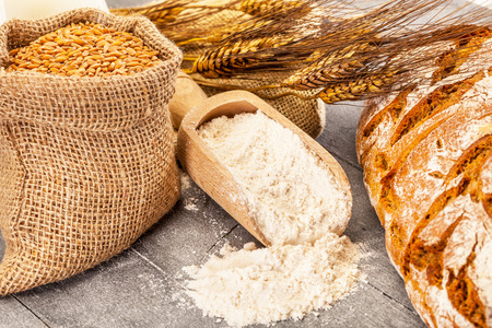Photo of wheat grains and flour on the wooden table Stock Photo