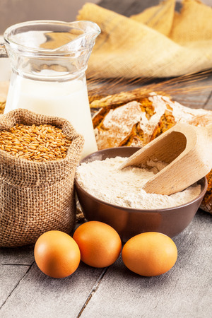 grains: Photo of wheat grains and flour on the wooden table Stock Photo