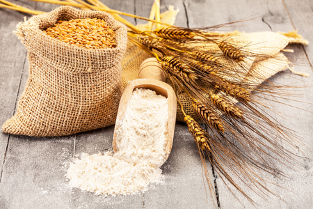 Photo of wheat grains and flour on the wooden table Banque d'images