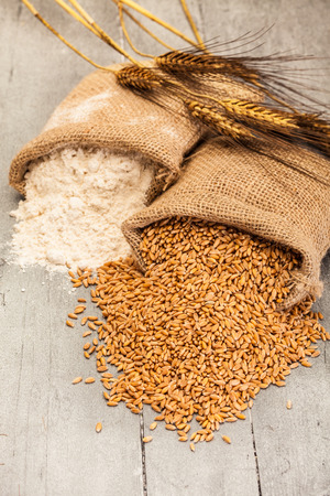 Photo of wheat grains and flour on the wooden table Standard-Bild