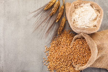 Photo of wheat grains and flour on the wooden table Stockfoto