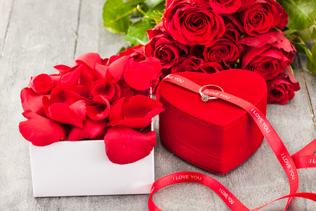 rose ring: Photo of ring and red roses over wooden table