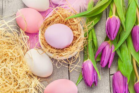 huevo: Vista desde arriba de los huevos de Pascua de color rosa y tulipanes de color violeta sobre la mesa de madera Foto de archivo