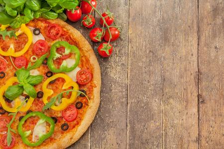 木製のテーブルの上にパプリカとおいしいピザの写真 写真素材