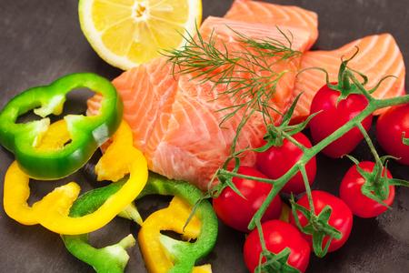 野菜黒背景の上に新鮮なおいしいサーモンの写真