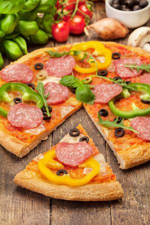 サラミと木製のテーブルの上にパプリカのピザの写真