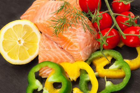 Photo of fresh tasty salmon with vegetables over black background