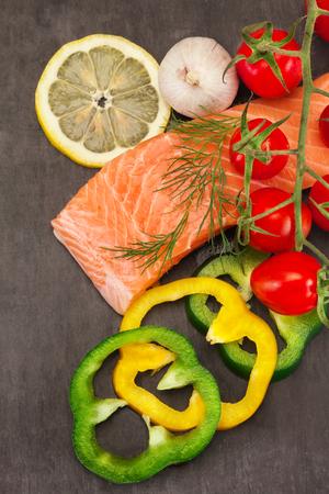 野菜黒背景の上に新鮮なおいしいサーモンの写真 写真素材 - 58371483