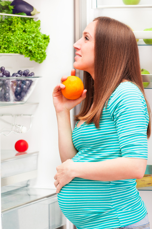 冷蔵庫の前に妊娠中の女性の写真