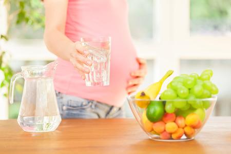 水のガラスを保持している笑顔の妊娠中の女性の写真 写真素材