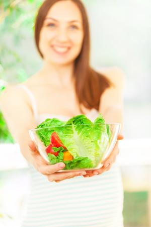 サラダを食べて笑顔の白人女性の写真