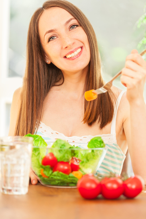 Photo of smiling caucasian woman eating salad
