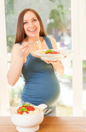 トマトソース パスタの巨大な部分を食べて妊娠中の女性の写真