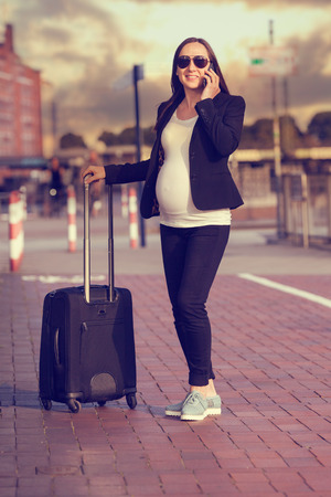 Photo of pregnant business woman talking on phone
