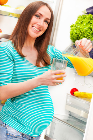 Photo of pregnant woman pouring orange juice in glass