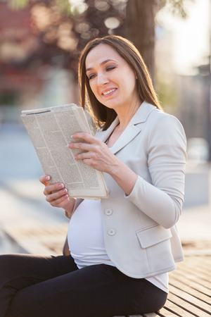 Photo of pregnant businesswoman  reading the newspaper on a bench Zdjęcie Seryjne