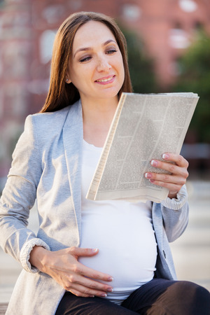 Photo of pregnant business woman reading the newspaper on a bench