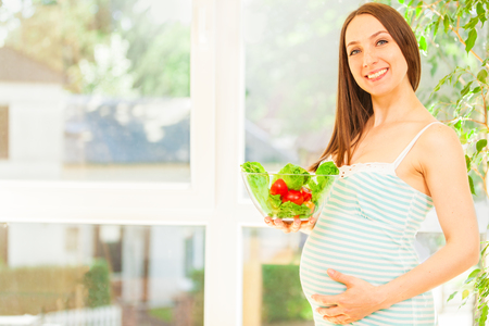 Photo of smiling pregnant woman eating salad