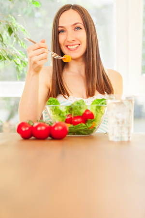 Photo of smiling caucasian woman eating salad photo