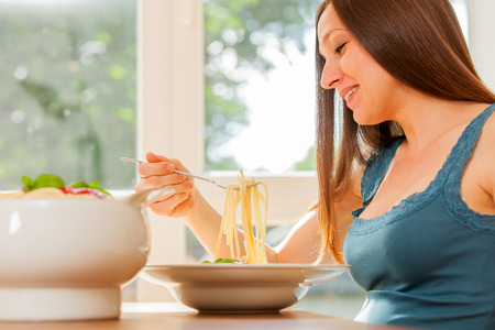 Photo of pregnant woman eating huge portion of pasta with tomato sauce photo