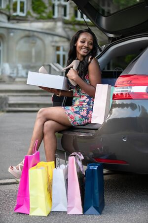 Young african woman is sitting on car trunk and looking at shoes she has just bought