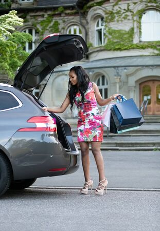 Young african woman is putting her purchases in car trunk Stock Photo