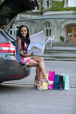Young african woman is sitting on car trunk and looking at shoes she have just bought Stock Photo