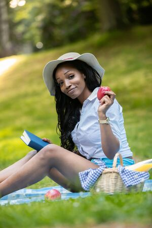 Attractive african woman is reading a book at picnic