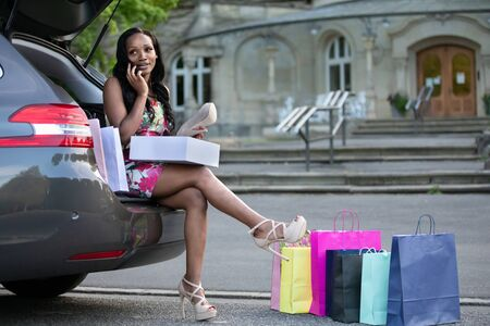 Young african woman is sitting on car trunk and looking at shoes she has just bought while phoning Stock Photo