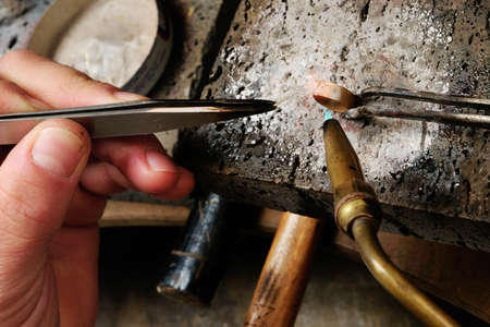 Skilled hands that create handmade jewelry with gold processing
