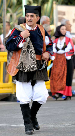 historical clothing: Nuoro, Sardinia, Italy - August 23, 2015: Parade of traditional costumes of Sardinia on the occasion of the Feast of the Redeemer of the Aug. 23, 2015 in Nuoro, Sardinia. Editorial