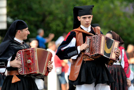 feast: Nuoro, Sardinia, Italy - August 23, 2015: Musicians in the parade of traditional costumes of Sardinia on the occasion of the Feast of the Redeemer of August 23, 2015 in Nuoro, Sardinia. Editorial