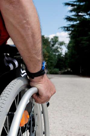paraplegic: La mano de un hombre que corre su silla de ruedas en un camino rural.