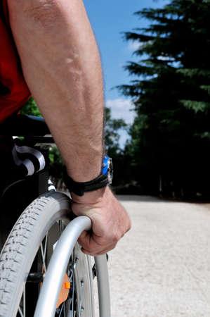 paraplegico: La mano de un hombre que corre su silla de ruedas en un camino rural.