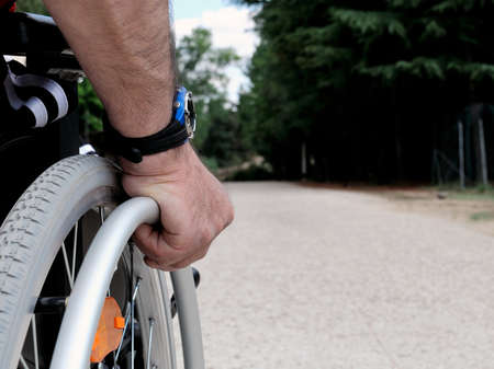 Hand of a man who runs her wheelchair in a country road. Stock Photo