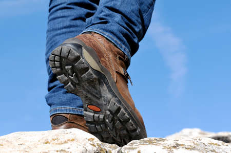 shoe strings: Walking on the rocks of a mountain trail with hiking boots Stock Photo