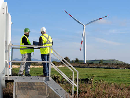 Technicians engaged in the detecting of a wind turbine installation for the production of energy Foto de archivo