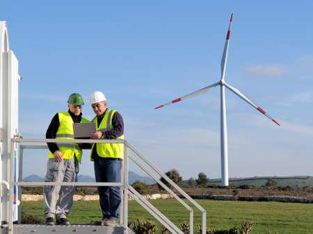 Technici die zich bezighouden met het detecteren van een windturbine installatie voor de productie van energie