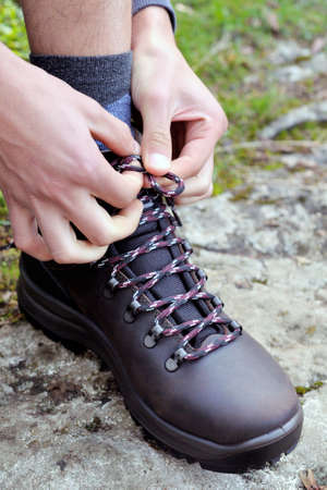 fasten: Fasten the laces of trekking shoes before the mountain walk Stock Photo