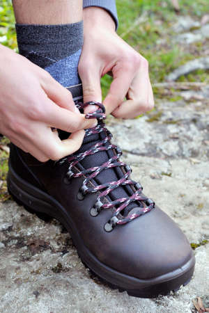 shoe strings: Fasten the laces of trekking shoes before the mountain walk Stock Photo