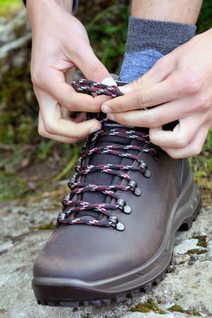 shoe string: Fasten the laces of trekking shoes before the mountain walk Stock Photo