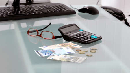 purchasing power: Desk modern office of a businessman with cash in euro, calculator and glasses Stock Photo