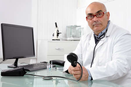 Cardiologist in his private practice with work equipment
