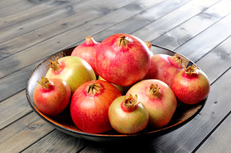 fruit bowl: Fruits of ripe pomegranate in a wooden fruit bowl on an antique wooden table