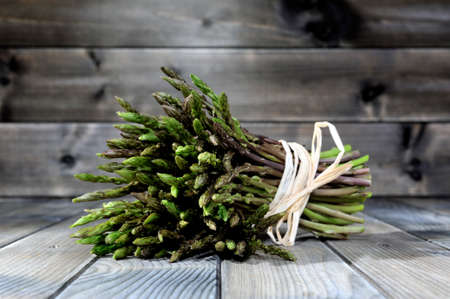 Fresh asparagus natural collected in countryside, photographed on an old wood table.
