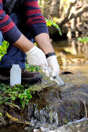 Biologist that collects samples in a water course for the analysis of its pollution and for the study of its characteristics.