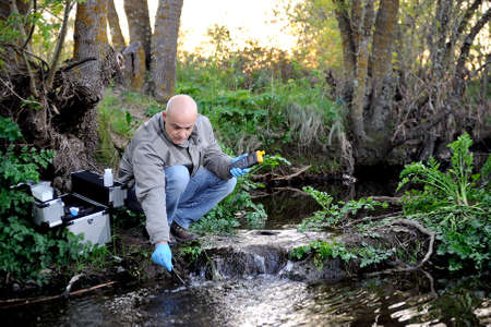 Biologist that collects data on temperature of a water course for the analysis of its pollution and for the study of its features. Stock Photo - 74470443